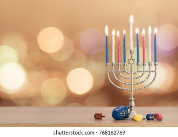 Hanukkah/ Chanukah Jewish holiday background with Hanukah/ Chanukkah menorah (Judaism candelabra) burning candles and traditional Dreidel game toy on wood table and on autumn light bokeh sun flare