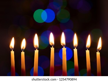 Hanukkah concept. Chanukah Candles flickering in front of out of focus christmas lights