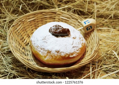 Hanukkah Donut or Doughnut (Sufganiyot in Israel) and Wood Dreidels. Hanukkah - Jewish Holiday. Symbols Hanukkah: Food and Toy. The dreidel has four sides, each of which is marked as a Hebrew sign