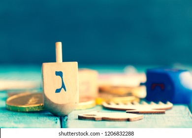 Hanukkah dreidels with some Hanukkah coins and Hanukkah candles on a vintage wood green background. Translation of the hebrew text: Letter G