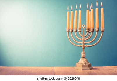 Hanukkah menorah with burning candles for holiday card background. Retro old style filtered photo