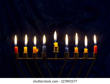 Hanukkah menorah (nine-branched candelabrum) with burning colored candles on a dark blue background