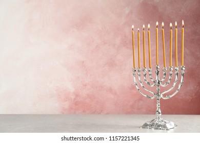 Hanukkah menorah on table against color background