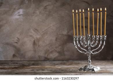 Hanukkah menorah on table against grey background
