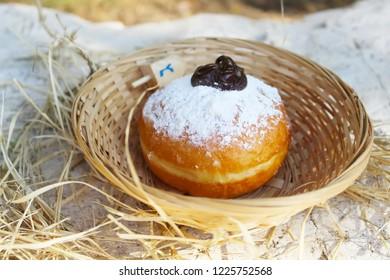 Hanukkah Sufganiyah (Sufganiyot in Israel). Hanukkah (Chanukah, Hanuka) - Jewish Holiday. Sufganiyah (Sufganiyot) - Festive Donut or Doughnut. Image of Jewish Holiday Hanukkah. Symbol Hanukkah, Food