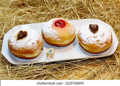 Hanukkah Sufganiyah (Sufganiyot in Israel, Donut) and Wood Dreidels. Hanukkah - Jewish Holiday. Symbols Hanukkah: Food and Toy. The dreidel has four sides, each of which is marked as a Hebrew sign