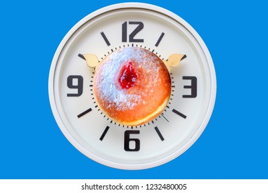 Hanukkah time. Clock with candles instead of arrows and tasty Jelly Doughnuts with jam. Chanukah celebration concept.