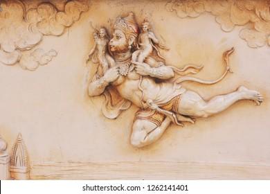 Hanuman carries Rama and Lakshman on his back. Flying Hanuman on the wall of a Hindu temple.