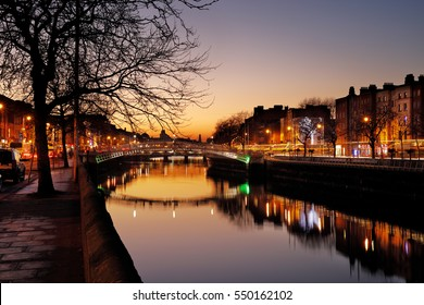 Ha'penny Bridge and the north banks of the river Liffey in Dublin City Centre at night. Ha'penny Bridge is a pedestrian bridge built in 1816 of cast iron