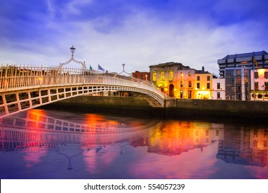 Ha'penny Bridge of the River Liffey in Dublin Ireland in the evening with lights and reflections