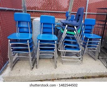 Haphazard stacks of blue school chairs