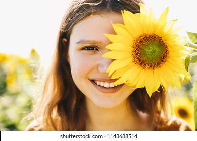 Hapiness. Sunflower. Beautiful cheerful young girl with sunflower enjoying nature and laughing on Summer sun flower field. Sunflare, sunbeams, glow sun. Backlight. Close up portrait