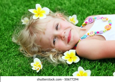 happi little girl with flowers plumeria lies on the grass