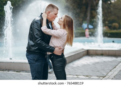 happily in love couple hugging by the water fountain