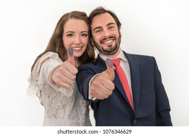 Happily married couple Young bride and groom showing their thumbs up