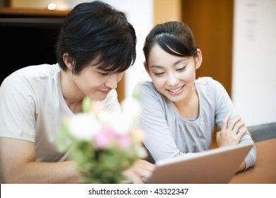 A happily young couple is watching PC together