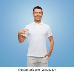 happiness, advertisement, fashion, gesture and people concept - smiling man in t-shirt pointing finger on himself over blue background
