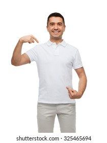 happiness, advertisement, fashion, gesture and people concept - smiling man in t-shirt pointing fingers on himself