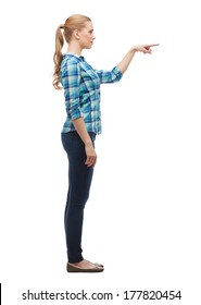 happiness, advertising and people concept - smiling young woman choosing something in the air