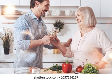 Happiness in the air. Positive aged woman standing in the kitchen with her adult son and drinking wine while resting together