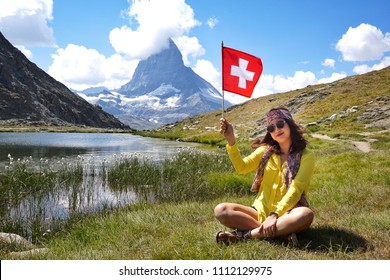 Happiness Asian beauty young tourists sitting and smiling with hand holding Swiss flag near the alpine lake of Riffelhorn in front of mountain Matterhorn peak, Zermatt, Switzerland.Summer Vacation
