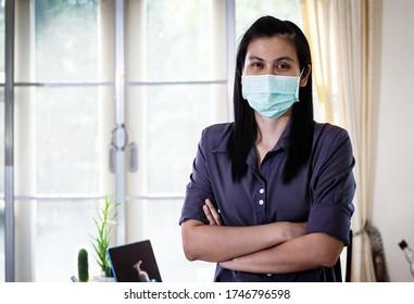 自宅のオフィスに防護マスクを付けたハピネスアジアのビジネスマンは、家庭のコンセプトから仕事を始めます。