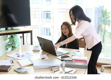 Happiness Asian businessmen people group explaining colleagues latest profit financial data in meeting room togetherness. Teamwork Togetherness Unity Variation Support Concept.