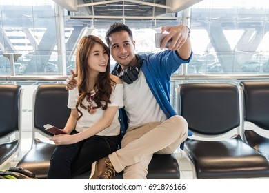 Happiness Asian couple traveler  taking a selfie with smart phone camera in smile action in modern an airport, travel and transportation with technology concept.
