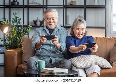 happiness asian retired couple enjoy playing and competition game smartphone mobile online together on sofa in living room home interior background,asian couple playing game together home isolate idea