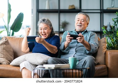 happiness asian retired couple enjoy playing and competition game smartphone mobile online together on sofa living room home interior background,asian couple playing game together home isolate ideas