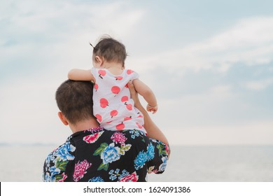 Happiness of Asian young father and baby daughter on the beach in summer holiday