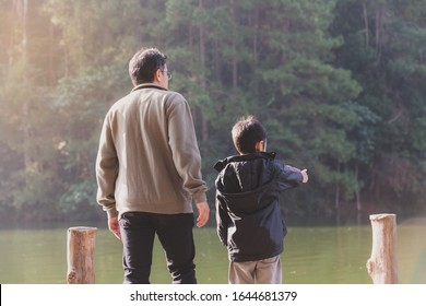 Happiness of Asian young father and son standing with talking together on a wooden bridge amid nature in the morning of tropical spring holidays