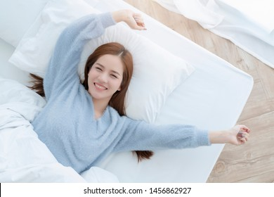 happiness beautiful asian woman smile morning wakeup on white bed soft pillow with morning daylight from window bedroom background
