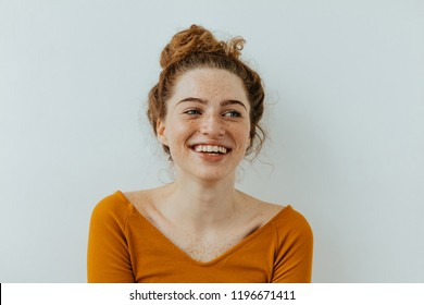Happiness. Beautiful blue eyed girl with freckles is looking away and laughing, on a white background