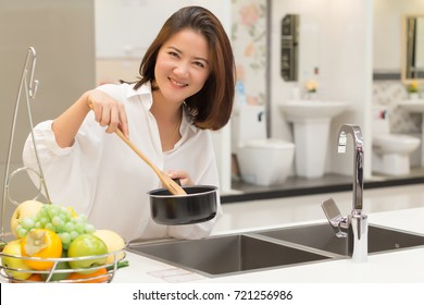 Happiness Beautiful Woman Holding Pan and Wooden Turner in The kitchen with Fruits in Basket Foreground. Asian Caucasian Female Model Portrait Concept. Copy Space for Text.