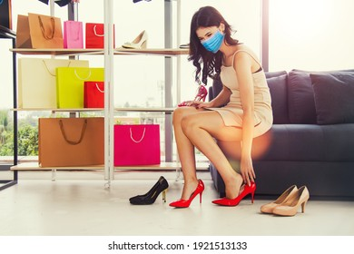 Happiness of beautiful women, masked customers, important people, shopping, choosing a favorite pair of red high heels on a comfortable sofa : Living new normal and Covid-19 epidemic