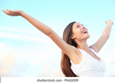 Happiness bliss freedom concept. Woman happy smiling joyful with arms up dancing on beach in summer during holidays travel. Beautiful young cheerful mixed race Asian Chinese / Caucasian female model.