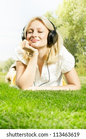Happiness blonde woman with headphones relaxing on green grass in the park.