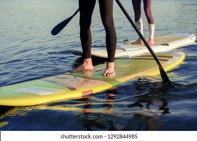 Happiness boy and girl on sup surf swimming at the river. Legs