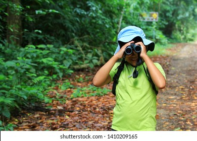 A happiness boy use binoculars with trail and green forest background