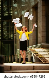 Happiness businesswoman celebrating success and throwing papers in the air in office district.