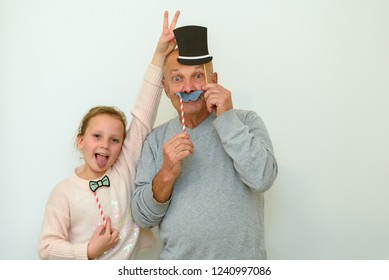 Close‑up Happiness. Candid shots of fun and happy expressions.  Portrait Of Real Happy Family Grandpa and Granddaughter In Festive Carnival Masks Having Fun In Home. Man eyes are wide open.