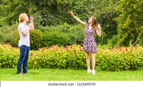 Happiness and carefree concept. Young woman and man having fun blowing soap bubbles together outdoor in park