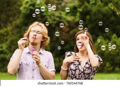 Happiness and carefree concept. Young woman and man having fun blowing soap bubbles together in park, green blurred background