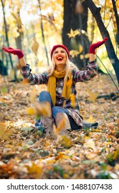 Happiness carefree woman relaxing in autumn park throwing leaves up in the air with arms raised up. Beautiful girl in colorful forest foliage, outdoor.