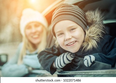 Happiness caucasian smilling boy with his mother looking out of black car window in sunny day at winter time near the forest.