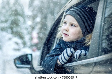 Happiness caucasian smilling boy looking out of black car window in sunny day at winter time near the forest.