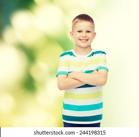happiness, childhood, ecology and people concept - smiling little boy in casual clothes with crossed arms over green background