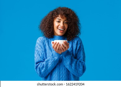 Happiness, comfort and cozy home concept. Happy relaxed and cheerful african american woman enjoying nice hot cup tea, smiling and gazing delighted, standing satisfied over blue background