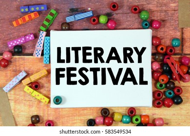 A happiness concept image of a colorful beads and cute clothespin scattered over a colorful wooden texture background with a white canvas and a word LITERARY FESTIVAL